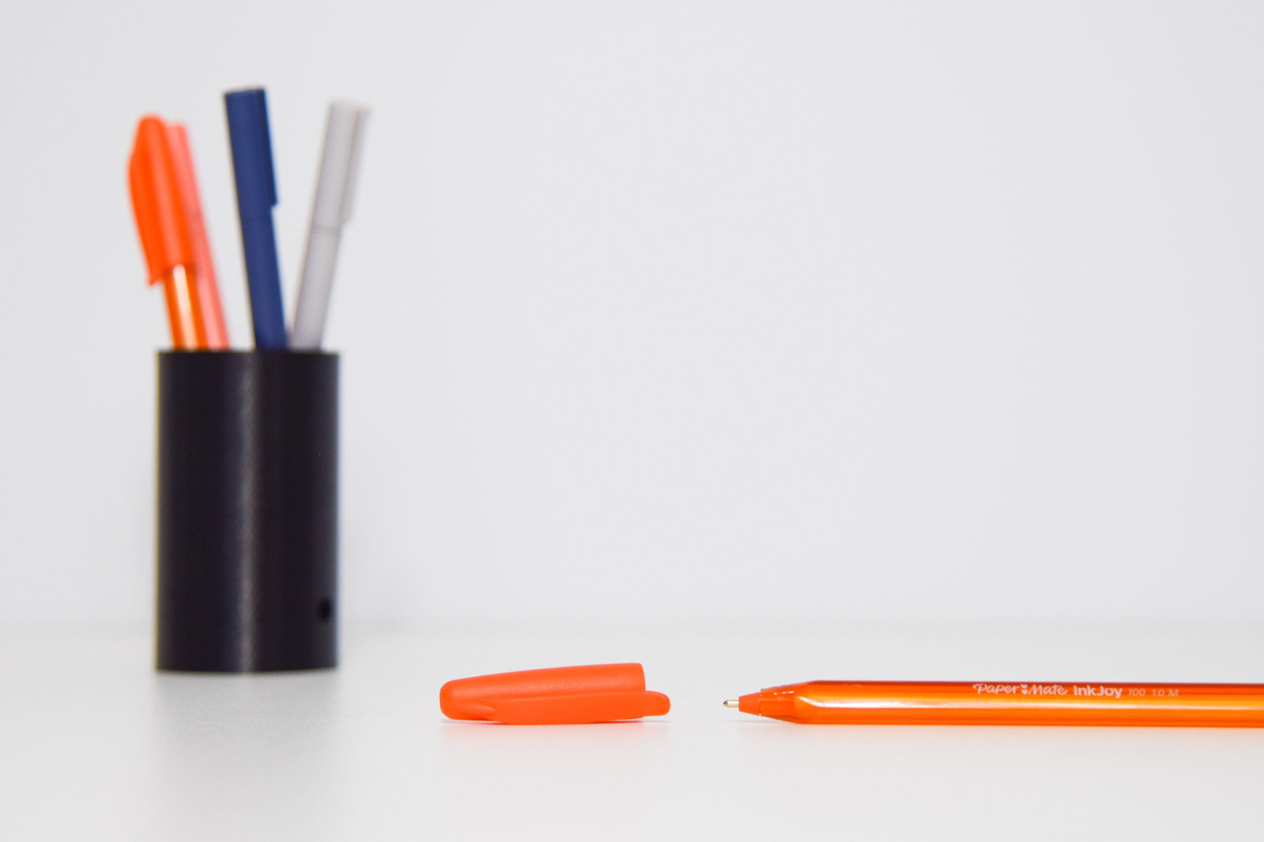 A black pen holder holds 4 pens (2 orange, 1 navy and 1 grey), and an orange pen lays with its cap off in front of it.